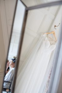 bride having make up done with wedding dress hanging Elmore court