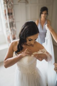 bride attaching wedding dress Elmore court photography
