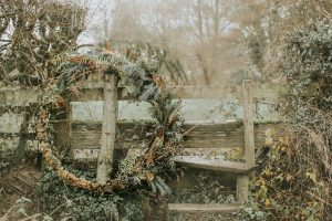 large wreath leaning on fence rustic wedding ideas