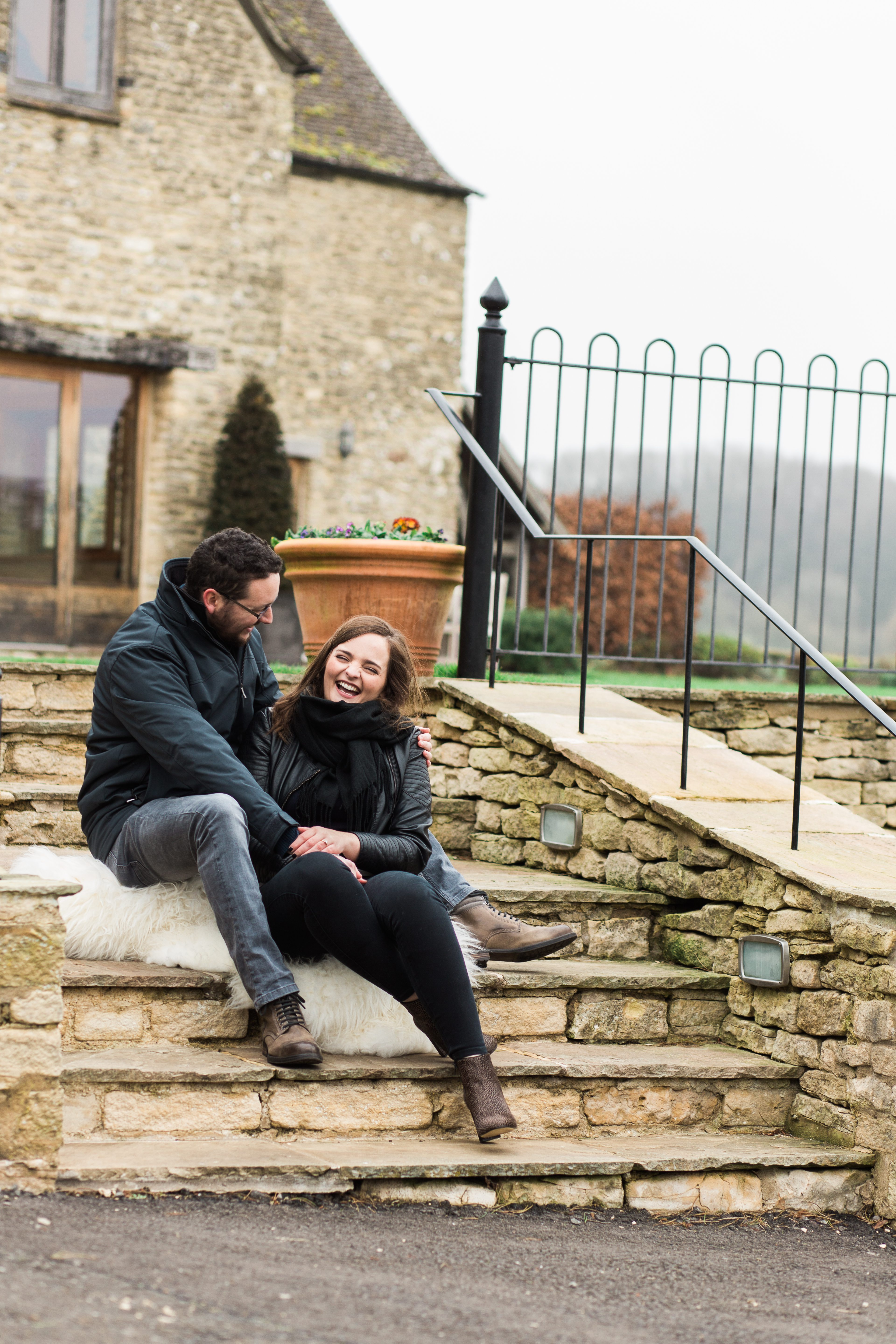 couple laughing on stairs for wedding photography at Kingscote Barn
