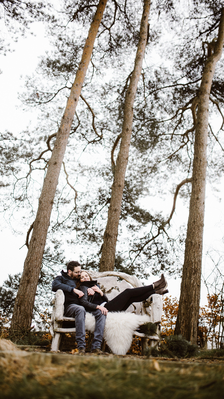 couple sitting on bench amongst trees Kingscote Barn wedding photographers