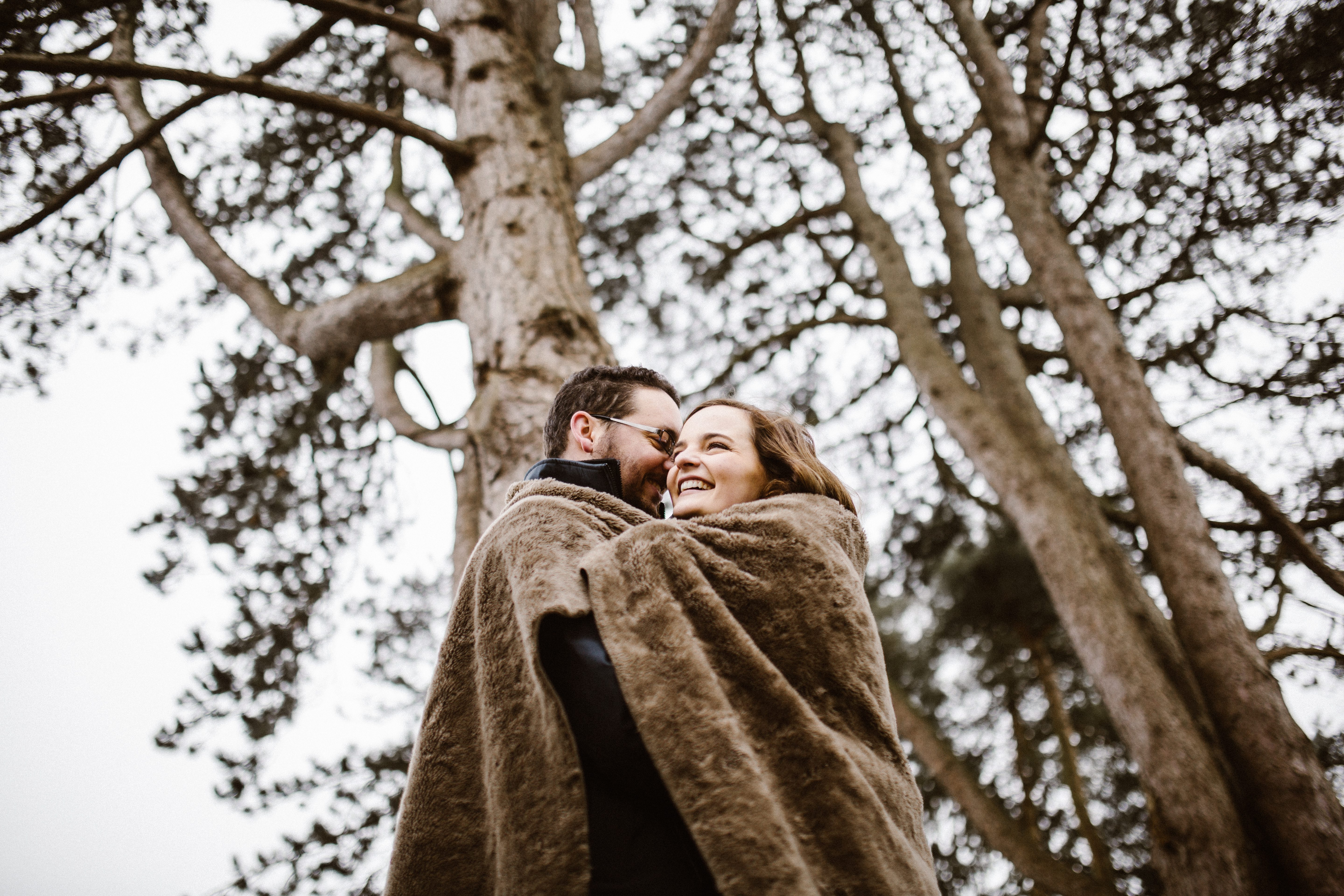cuddling couple on cold day at pre wedding shoot Kingscote Barn photography