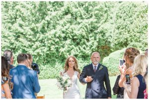 bride walking with father outdoor ceremony Barnsley house wedding photography