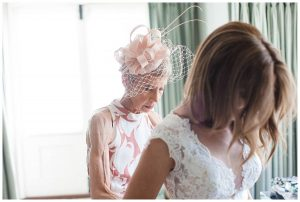 Mother of the bride doing up bride's dress Barnsley House Photographer