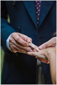 groom putting on wedding ring Barnsley House