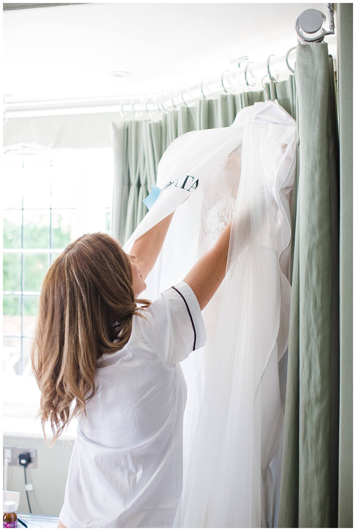 Bride uncovering Berta wedding dress Barnsley house wedding photographer