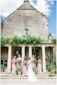 Barnsley House bridal party looking at Gloucestershire wedding photographer
