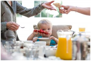 little boy eating breakfast with red spoon wedding day Barnsley house
