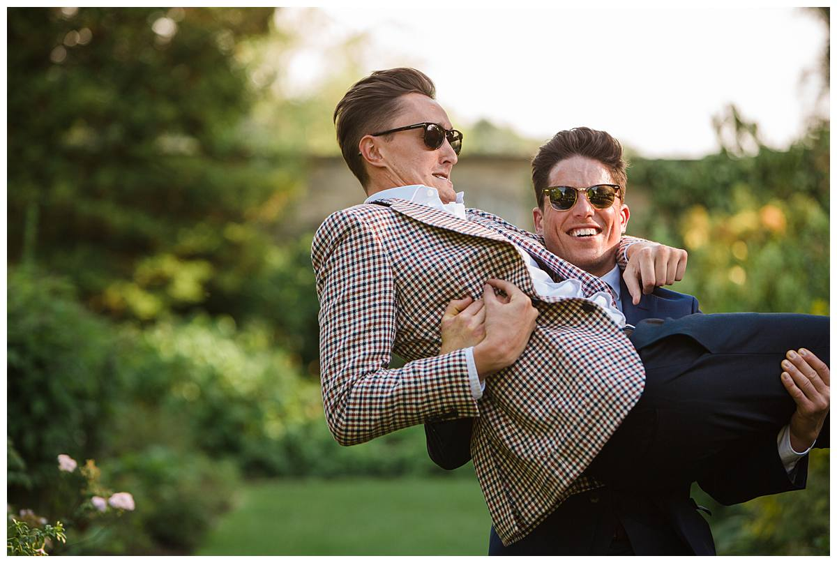 men lifting each other up Barnsley House for cotswold wedding photographer