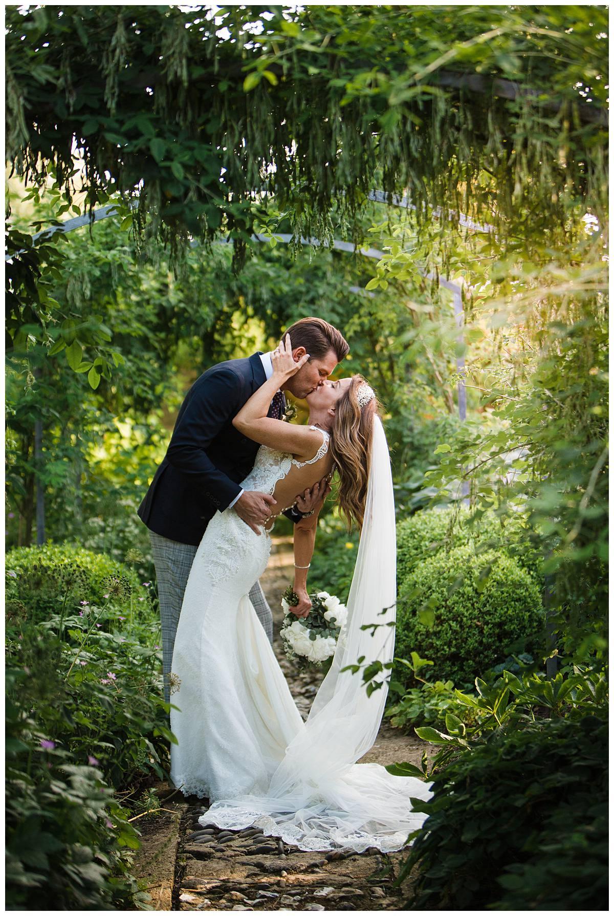 couple kissing in Barnsley House gardens for wedding photographer