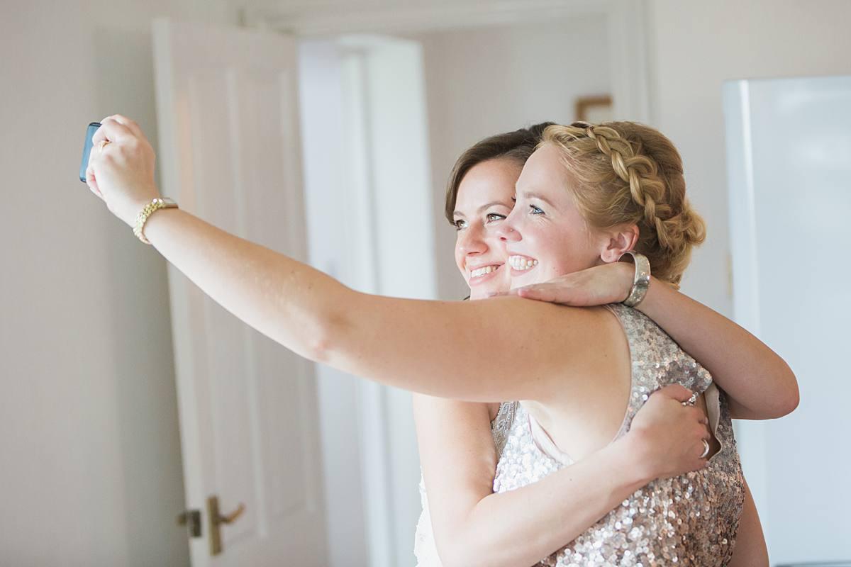 bride with bridesmaid making a selfie Glastonbury wedding photographer