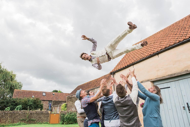 groomsmen throwing groom in the air bristol wedding photographers