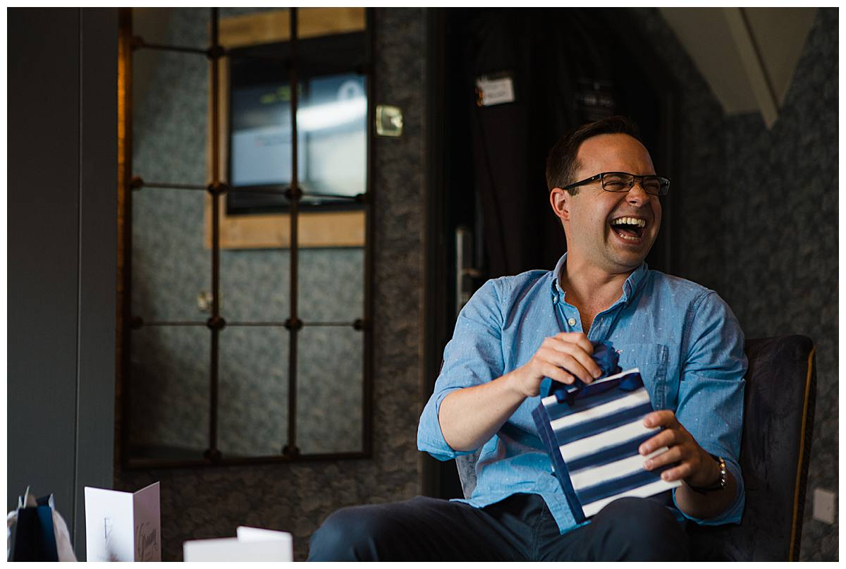groom laughing while getting his gift gloucestershire wedding