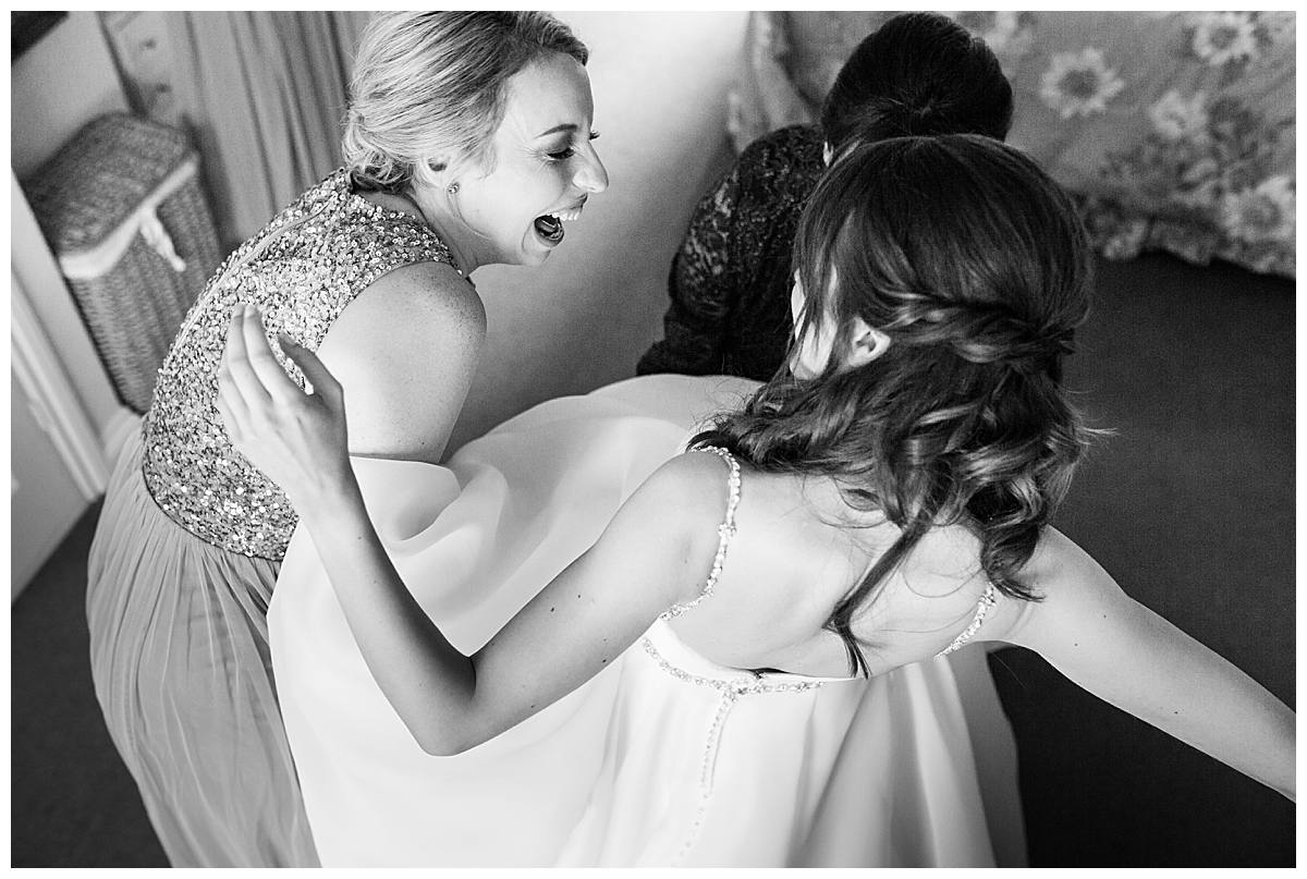 bridesmaid helping bride get ready for her wedding day