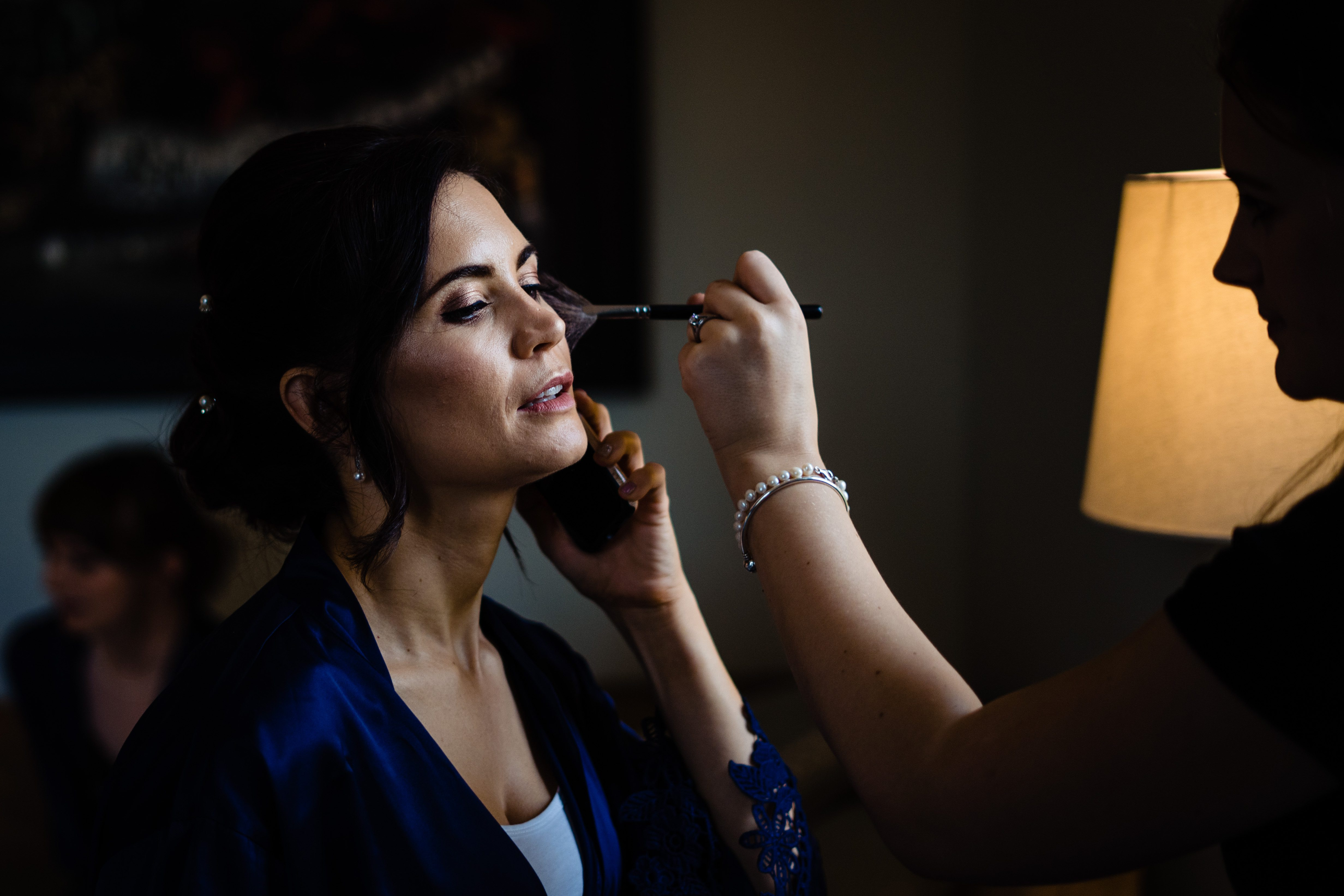 bridesmaid having makeup applied while on phone bowood hotel