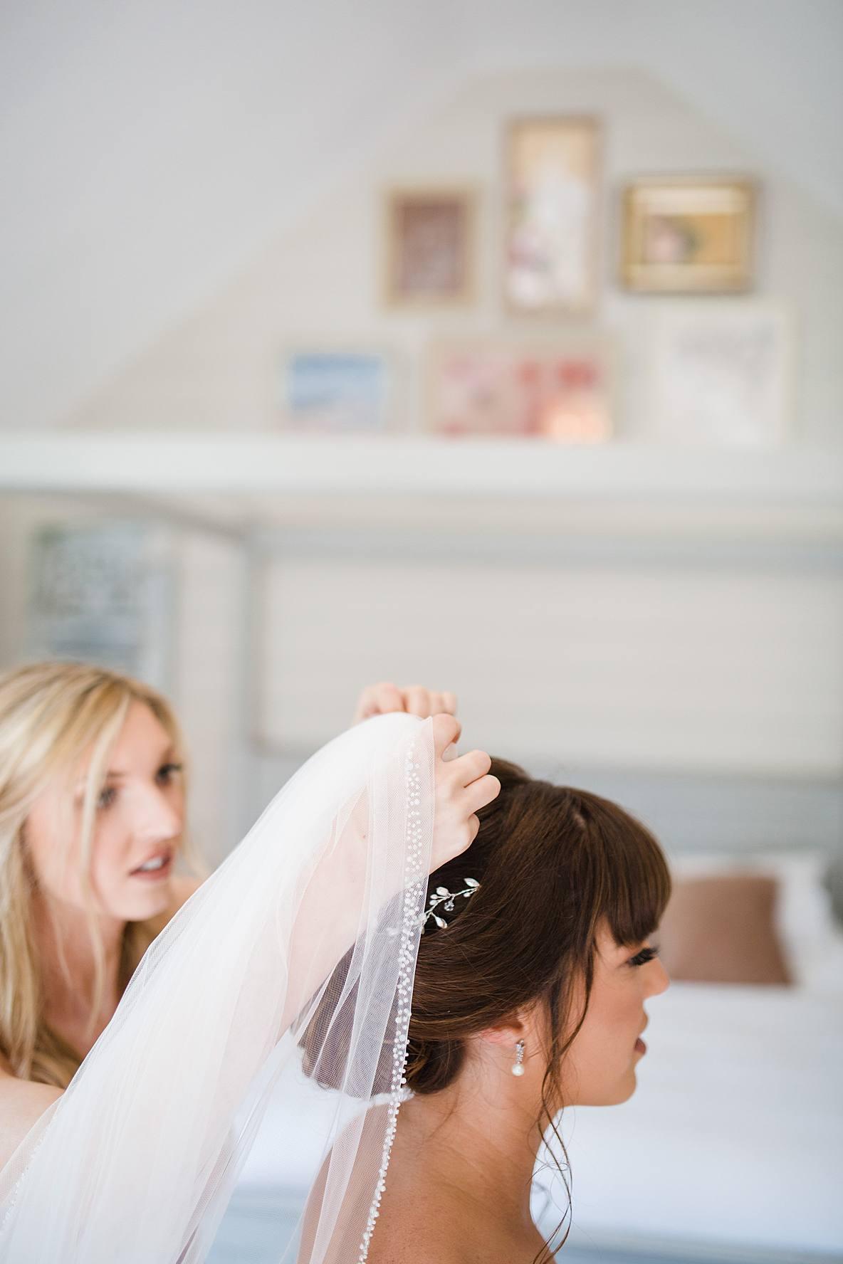 bridesmaids putting on veil