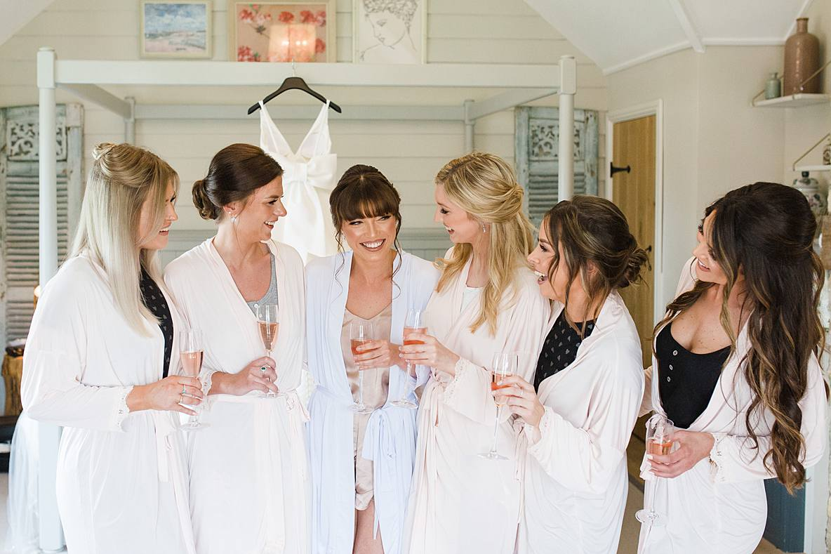 bride laughing with bridesmaids cotswold wedding