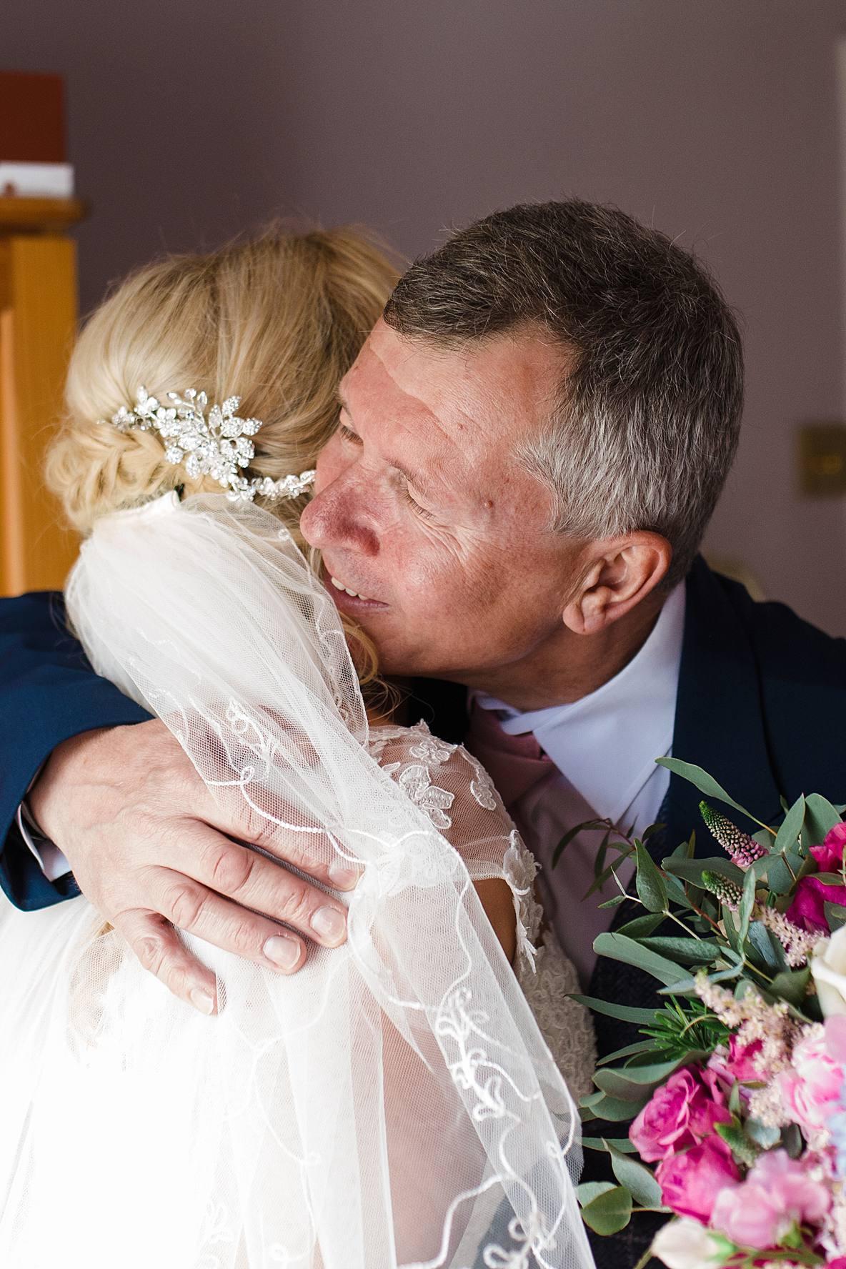 dad hugging bride on wedding day Kingscote Barn wedding