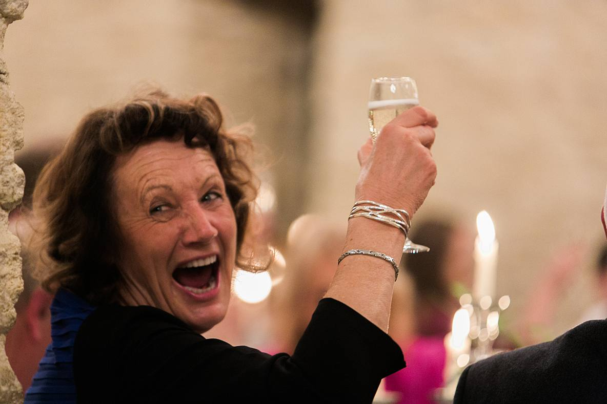 guest laughing saying cheers Kingscote Barn wedding photography