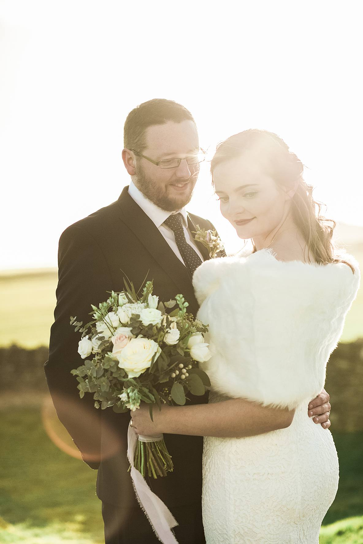 bride and groom with sunlight coming through Kingscote Barn wedding