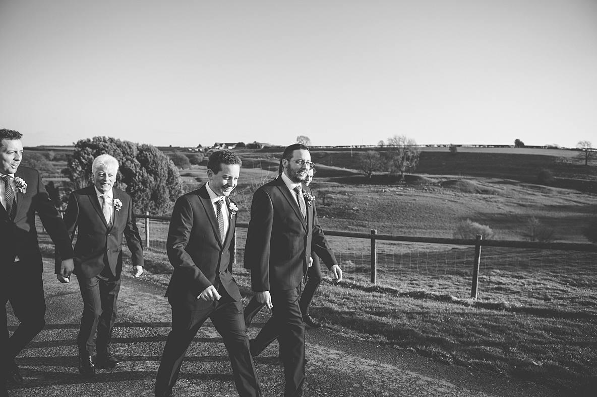 groomsmen walking near fields Kingscote Barn wedding winter