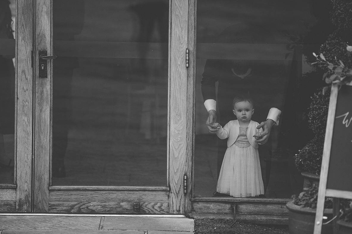 little girl looking out window Kingscote Barn January wedding