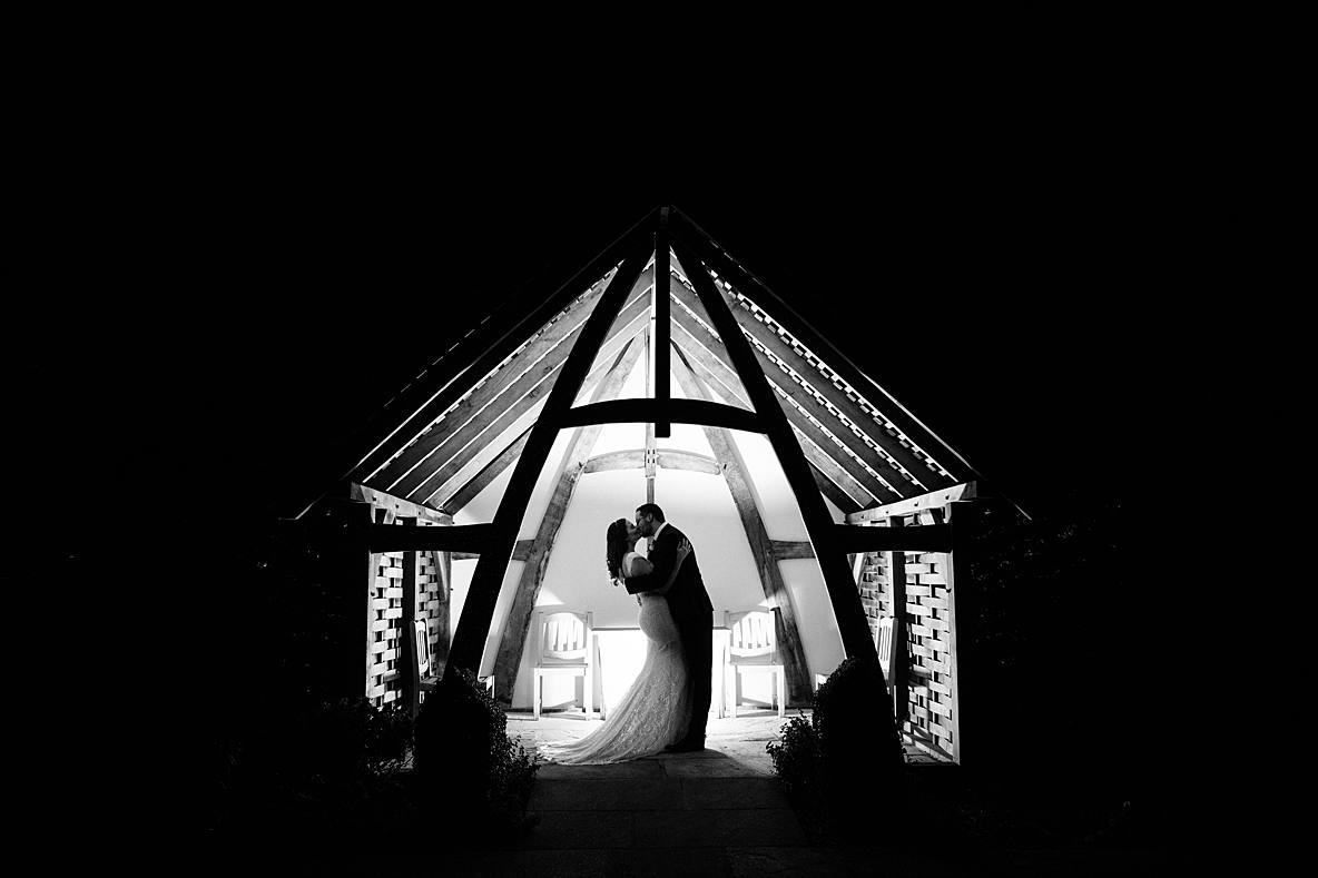 black and white wedding photographer Kingscote Barn couple kissing