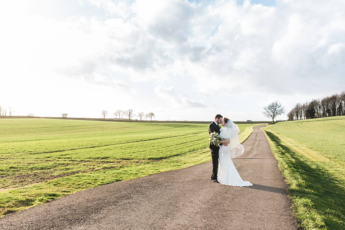 couple kissing in field Kingscote Barn January wedding photographer