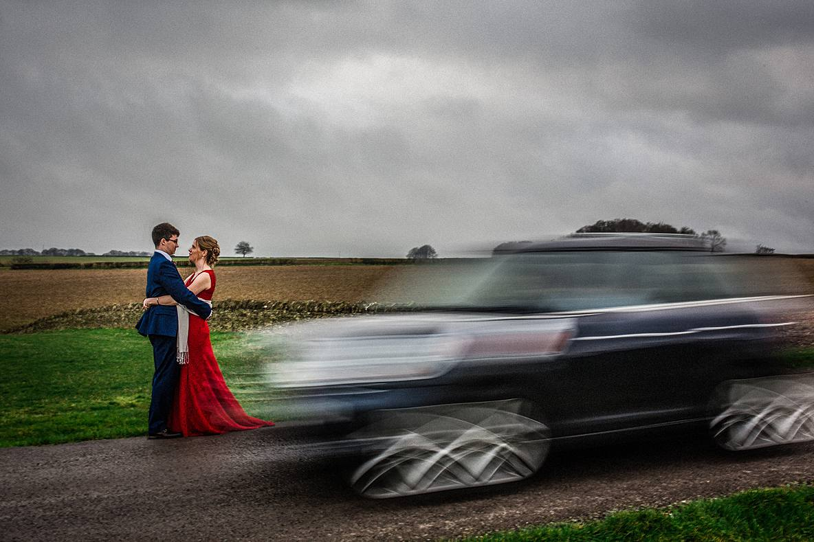 bride and groom hugging as car drives by Kingscote Barn