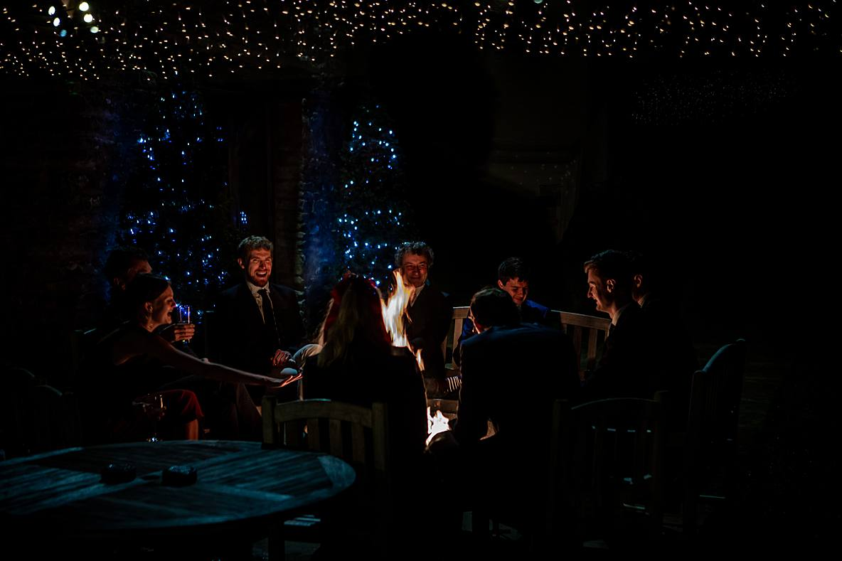 guests sitting around fire talking Kingscote Barn christmas wedding