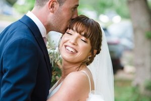 groom kissing bride at Frogmill Inn cotswold wedding venue