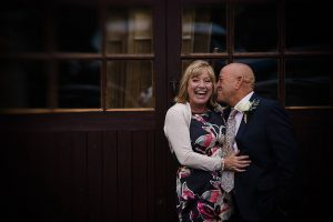 COUPLE CUDDLING AND LAUGHING FOR GLOUCESTERSHIRE WEDDING PHOTOGRAPHER