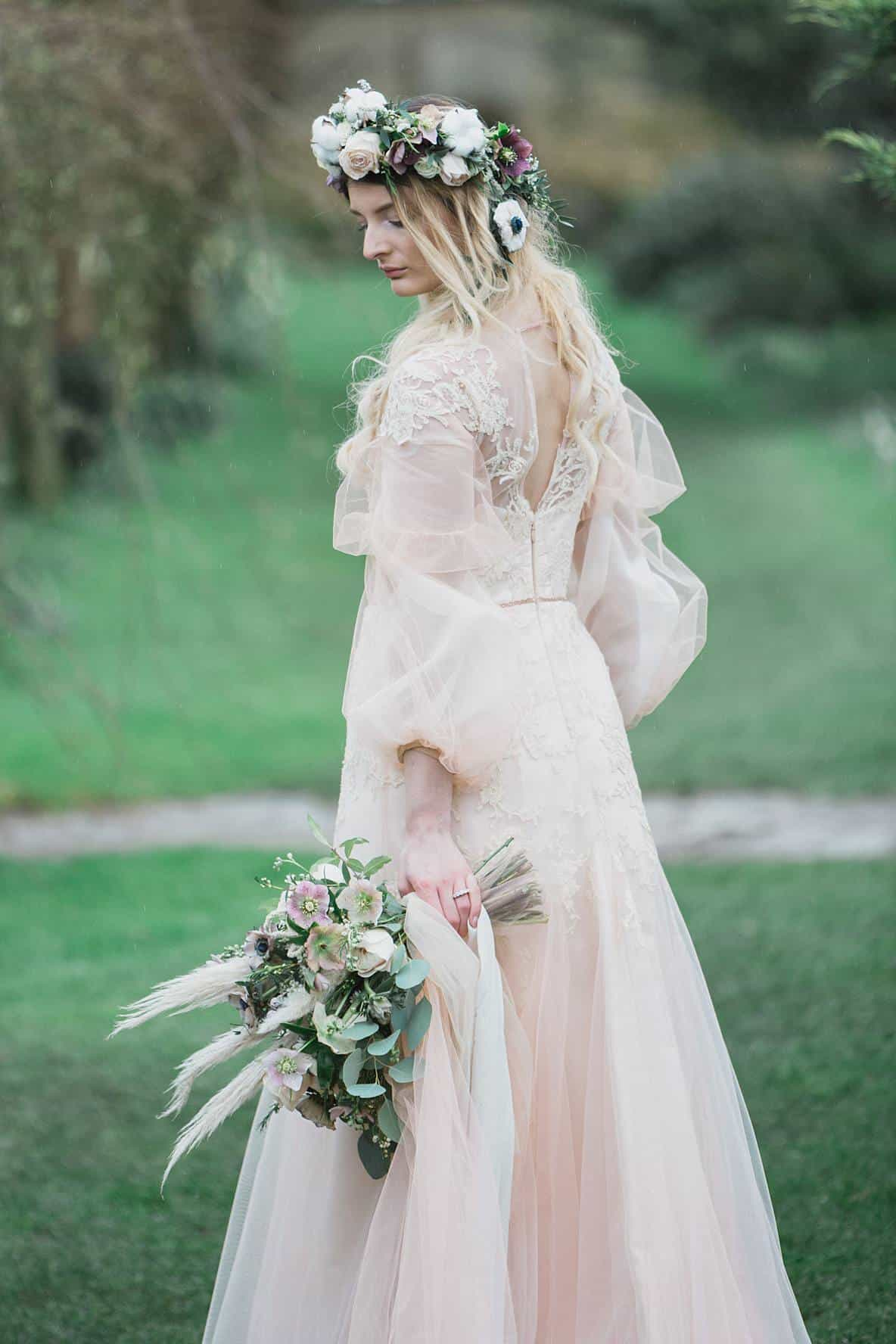bride looking at bouquet Barnsley House cotswolds
