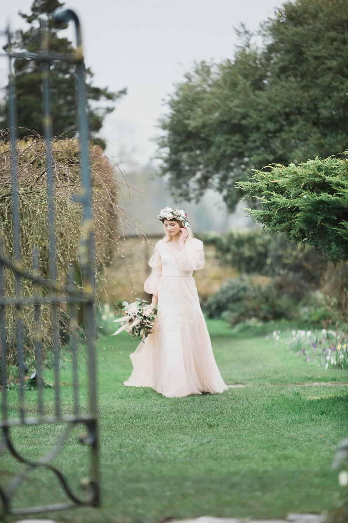 bride walking toward gate Barnsley House bibury wedding