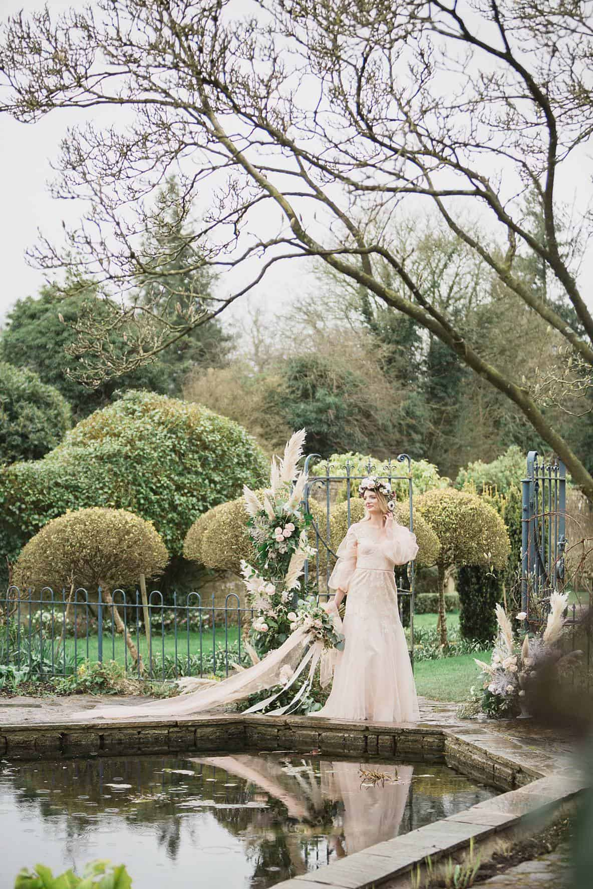 bride looking in water Barnsley House temple wedding photographer
