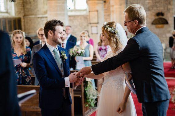 handing bride over micro wedding photographer