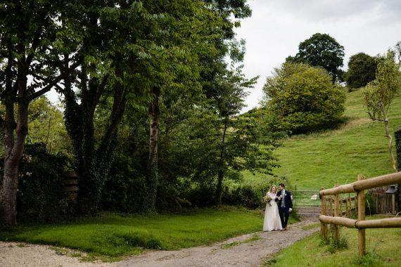 couple walking in field micro wedding photographer